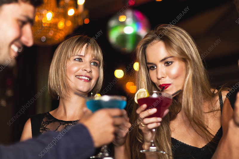 Smiling women having cocktails in club