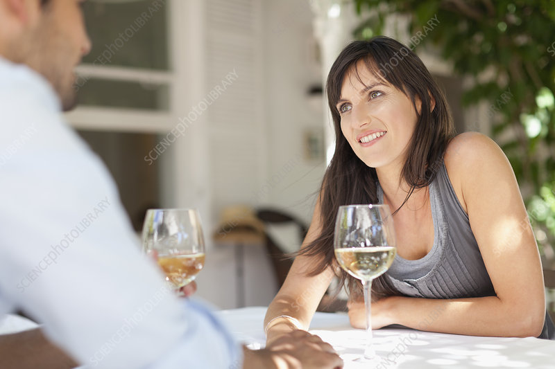 Couple having wine at table outdoors