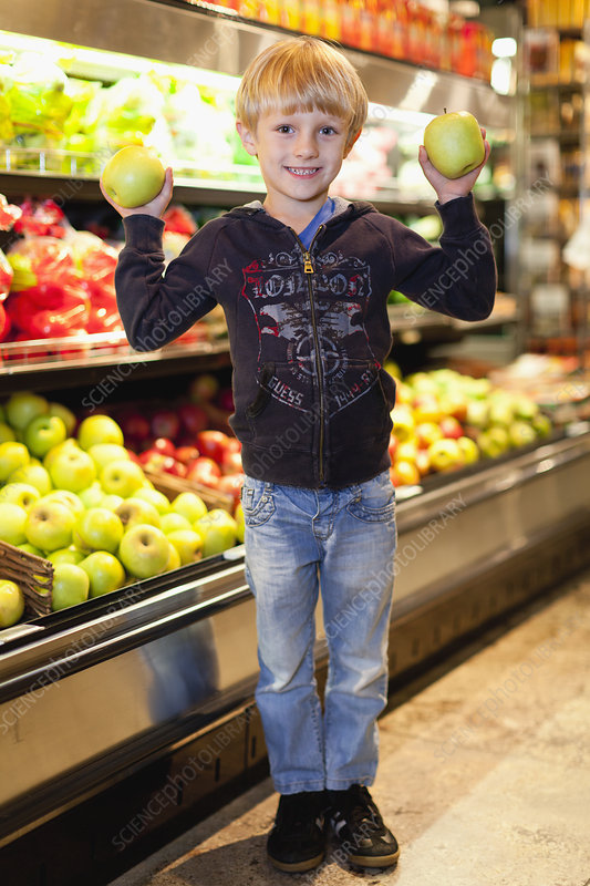 Boy holding fruit at grocery store