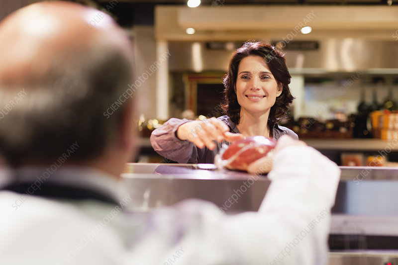 Woman buying meat from butcher