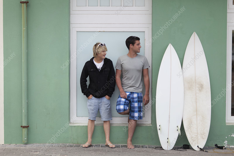 Teenage boys standing with surfboards
