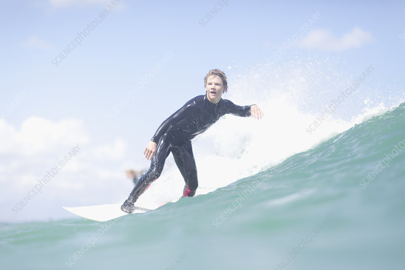Teenage surfer riding a wave