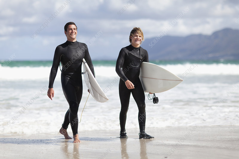 Teenage surfers carrying board on beach