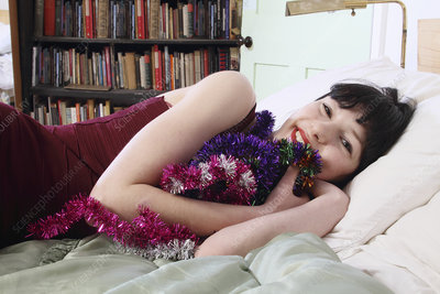 Smiling woman hugging tinsel in bed