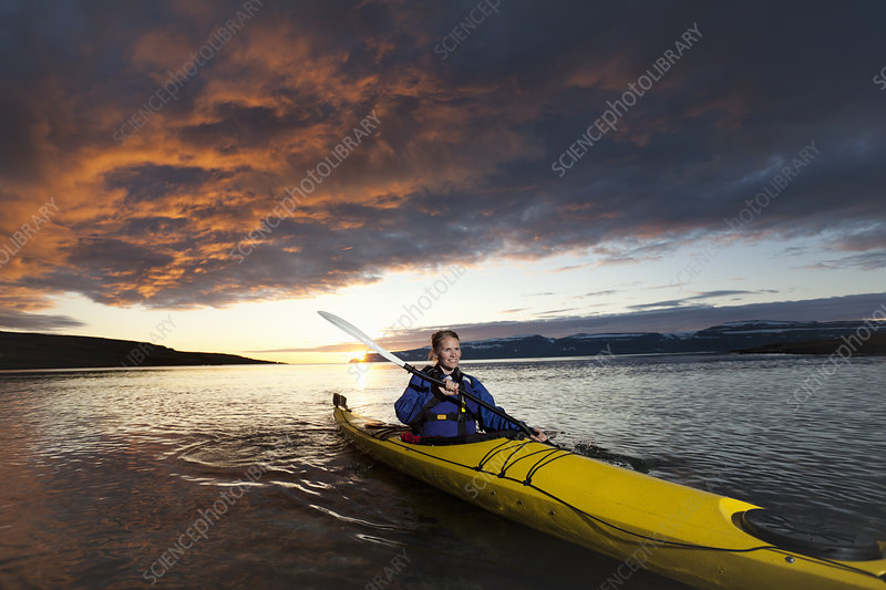 Woman kayaking in still lake