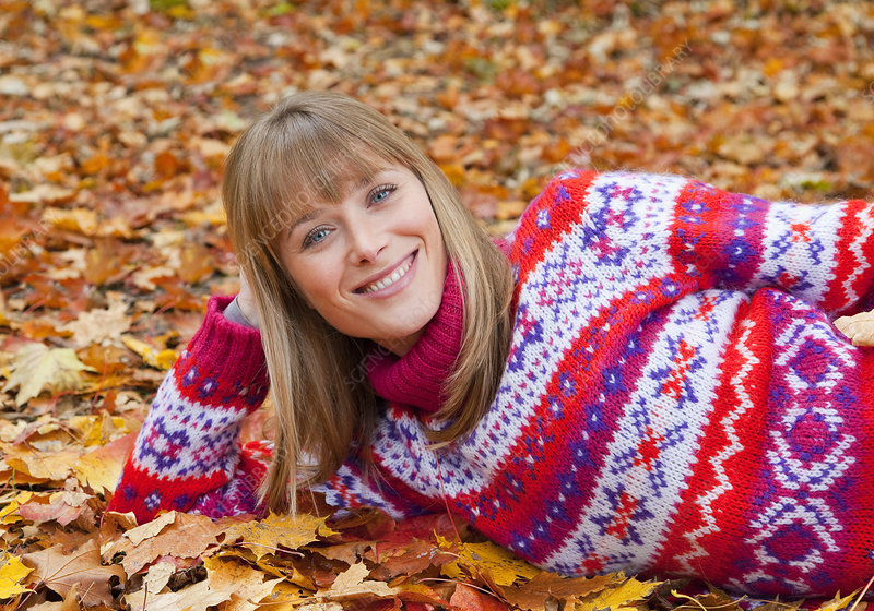 Smiling woman laying in fall leaves