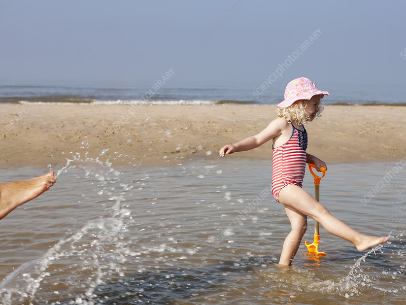 Child playing in water at beach