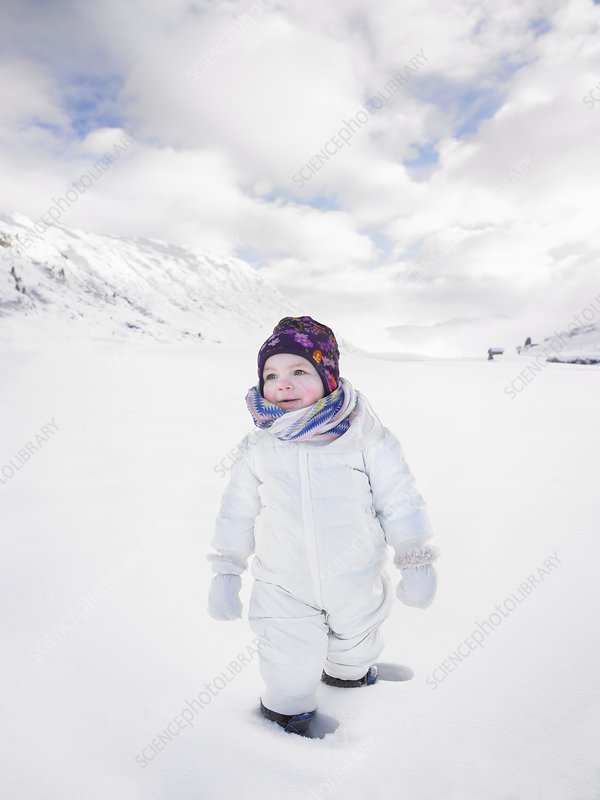 Toddler walking in snowy landscape