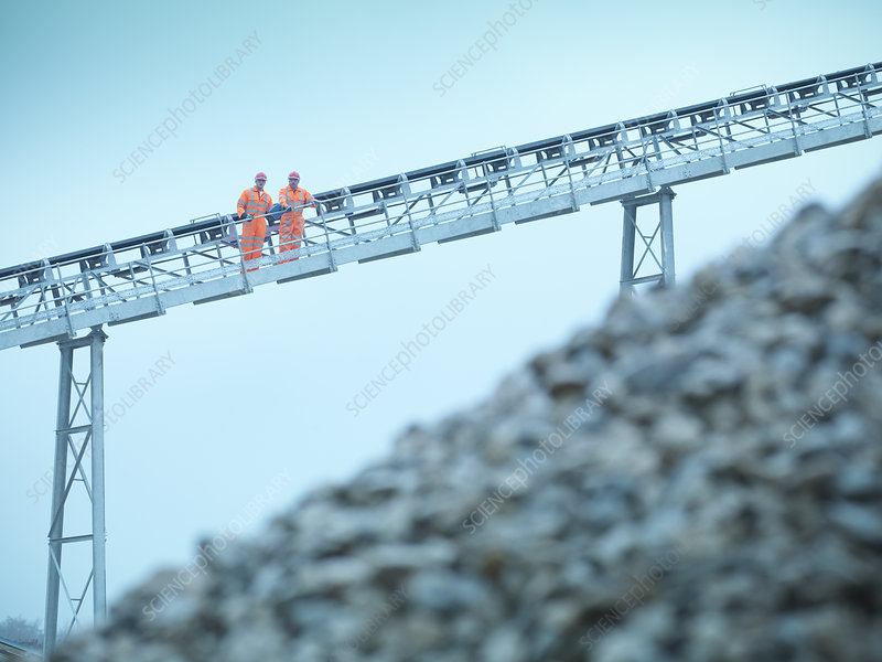 Worker climbing screening conveyor