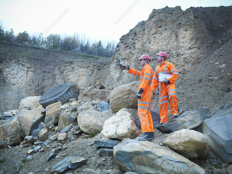 Workers examining rocks in quarry