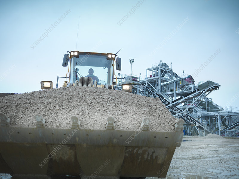 Worker driving digger with gravel