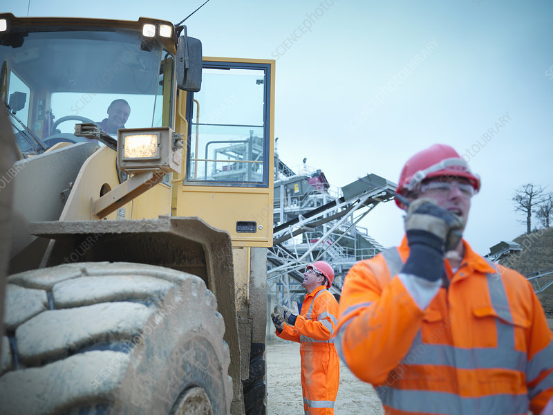 Worker talking to digger driver on site