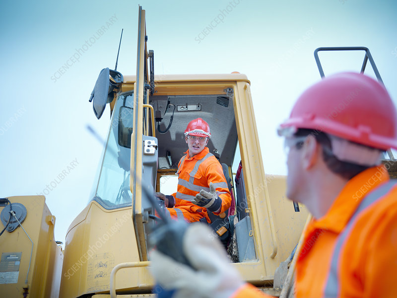 Worker driving industrial digger on site