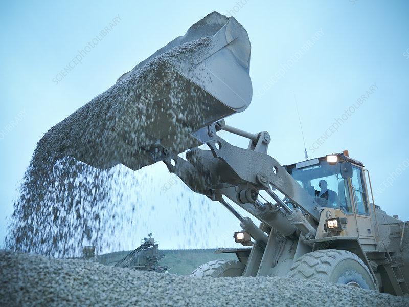 Worker shoveling quarry rock with digger