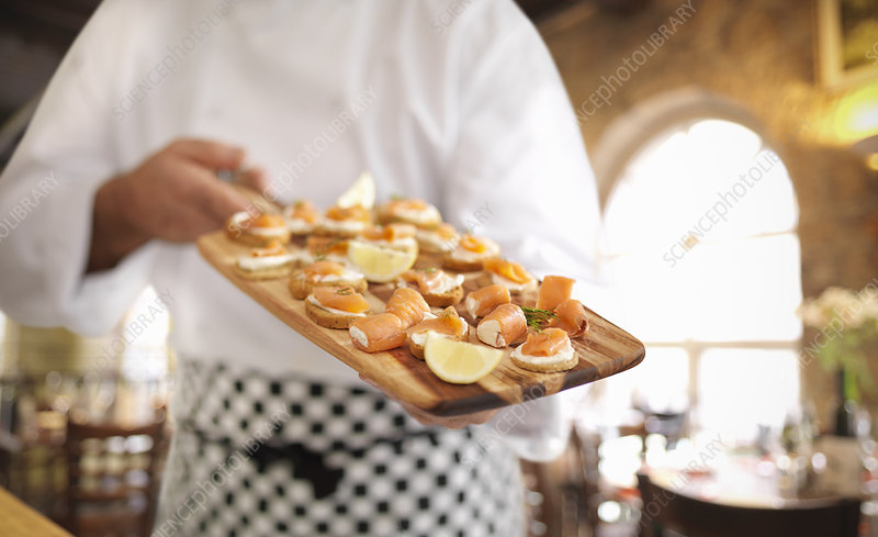 Chef with of salmon, cheese and crackers