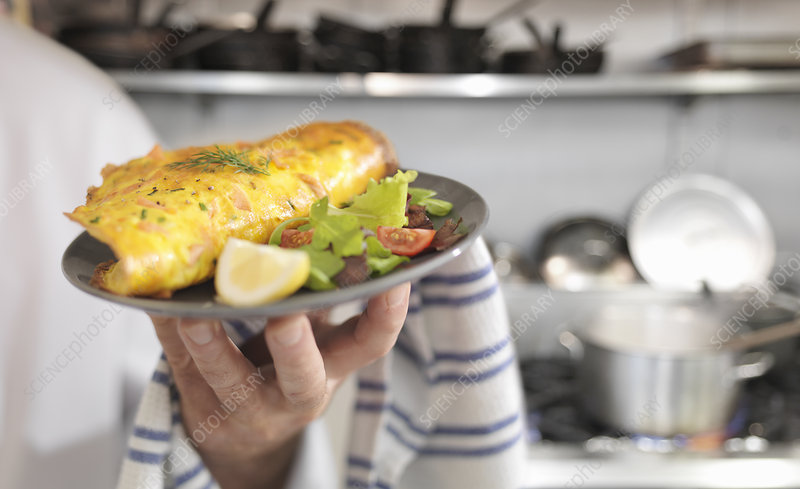 Chef holding salmon omelet and salad