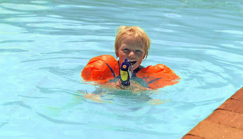 Boy playing with water gun in pool