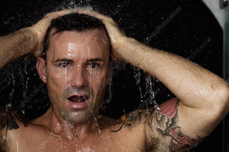 Man washing his hair in shower