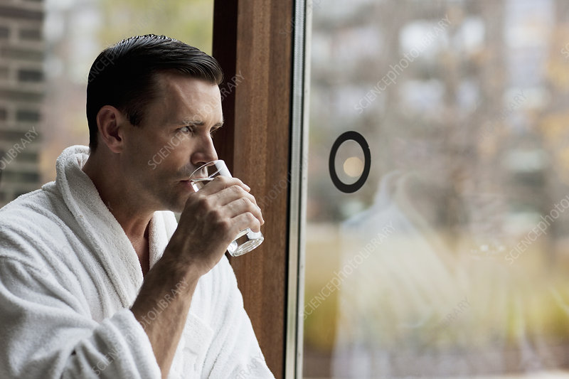 Man in bathrobe drinking water by window