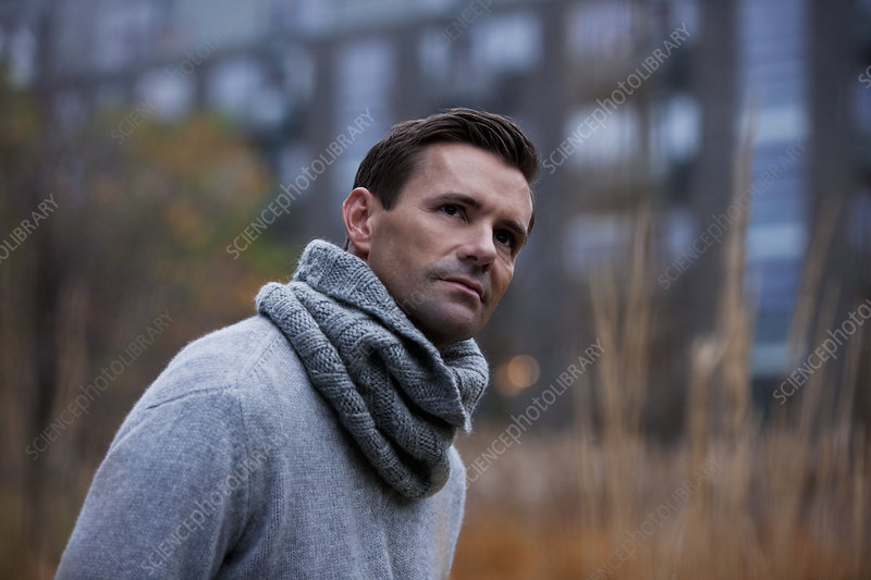 Man wearing knitted scarf outdoors