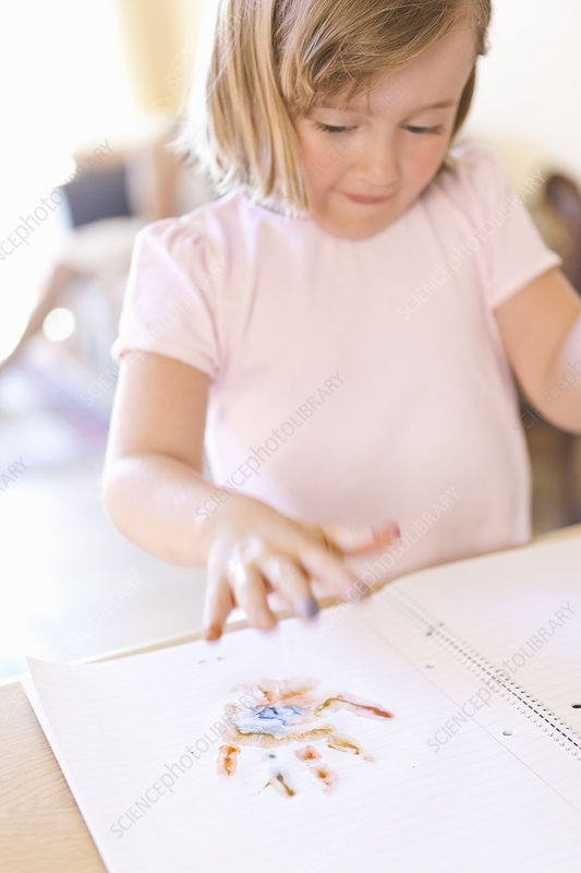 Girl finger-painting in notebook
