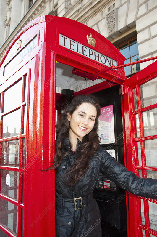 Woman smiling in red telephone booth