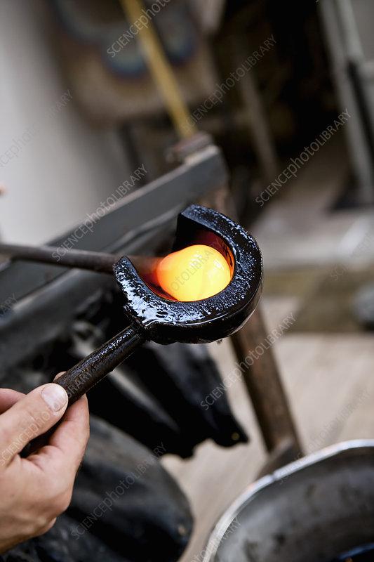 Glassblower shaping hot glass