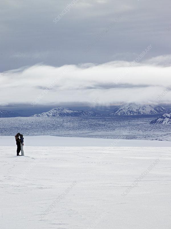 Couple hugging on snowy glacier