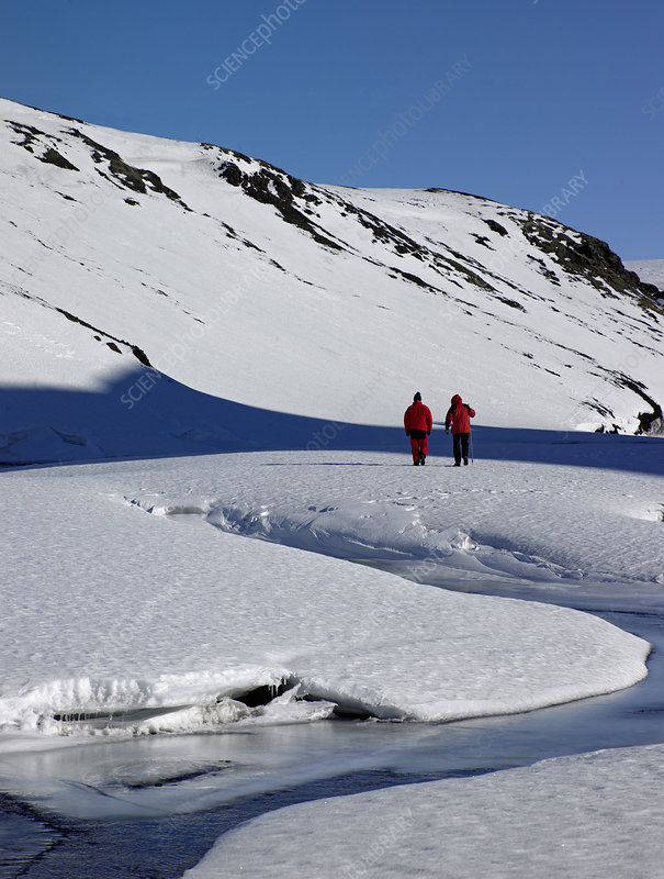 Couple hiking on snowy glacier