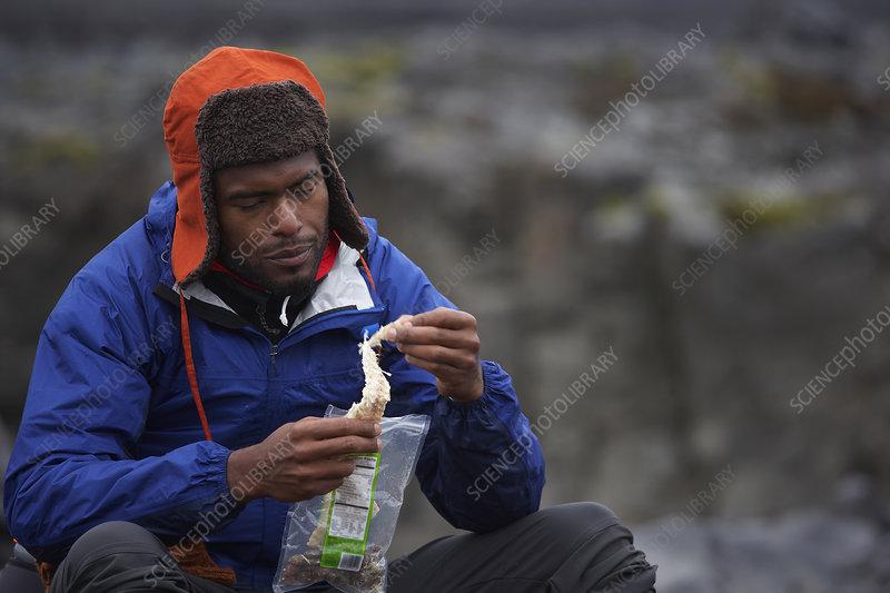 Man eating dried fish during hike