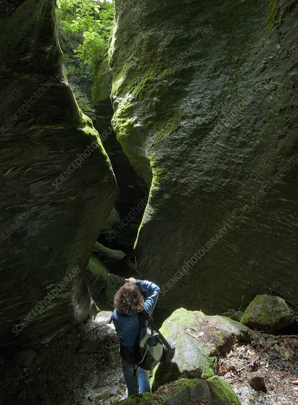 Woman taking pictures of rocky cavern
