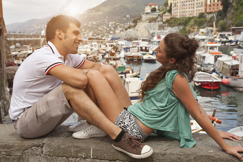 Couple relaxing on stone wall by pier