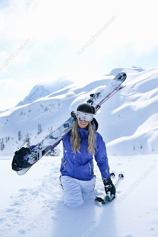 Skier carrying skis in snow