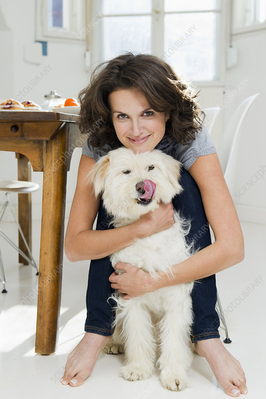 Woman hugging dog in kitchen