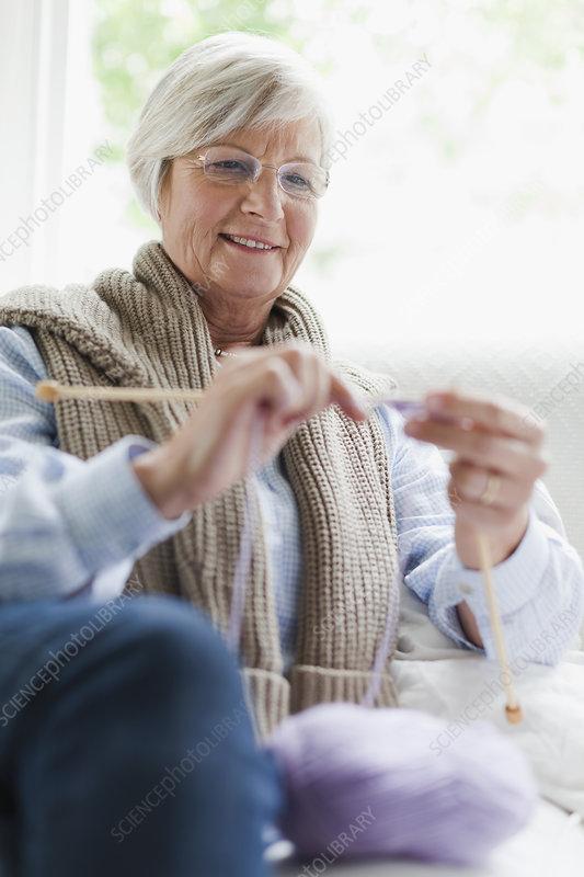 Smiling older woman knitting