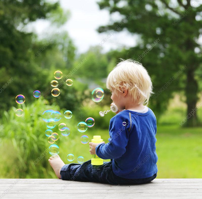 Boy blowing bubbles on porch