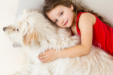 Girl relaxing in bed with dog