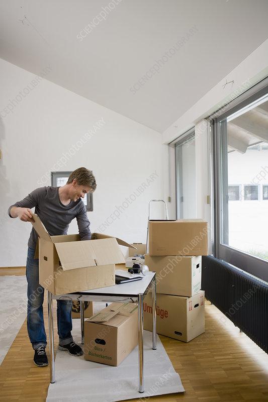 Man unpacking cardboard boxes