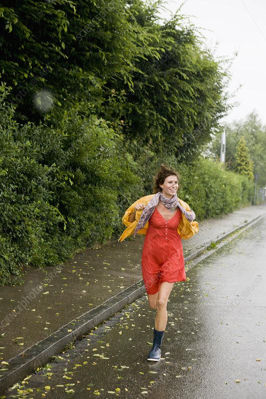Smiling woman running in rain
