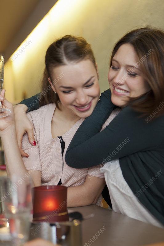 Smiling women hugging in cafe