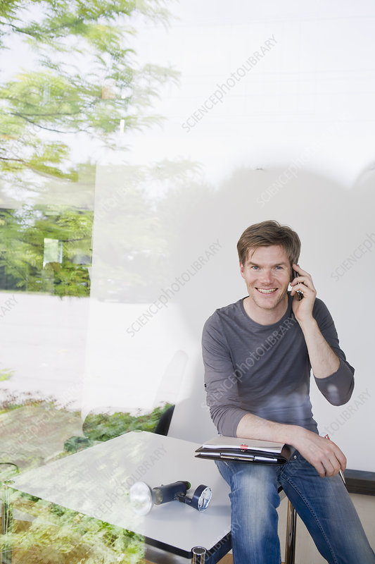 Man on cell phone taking notes