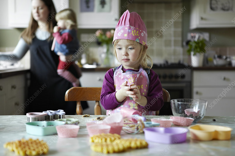 Toddler girl baking in kitchen