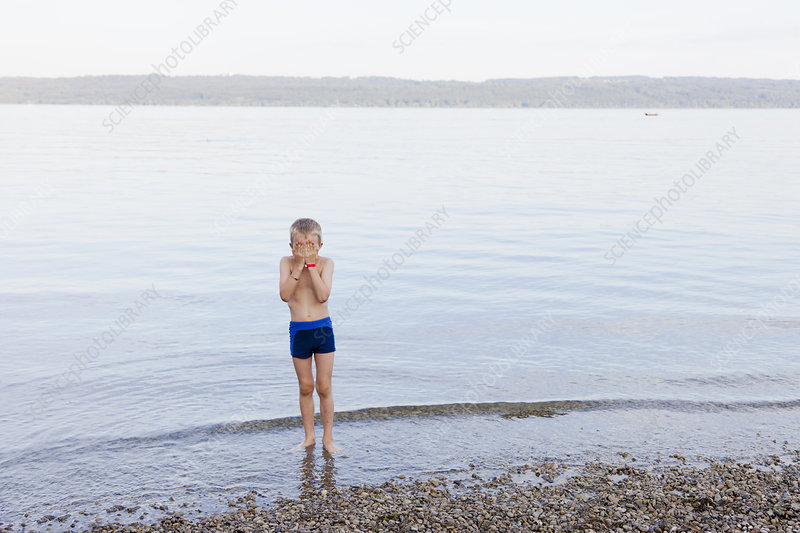 Boy covering his face on beach