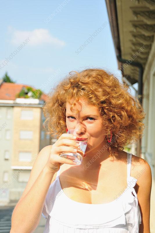 Woman drinking water on balcony