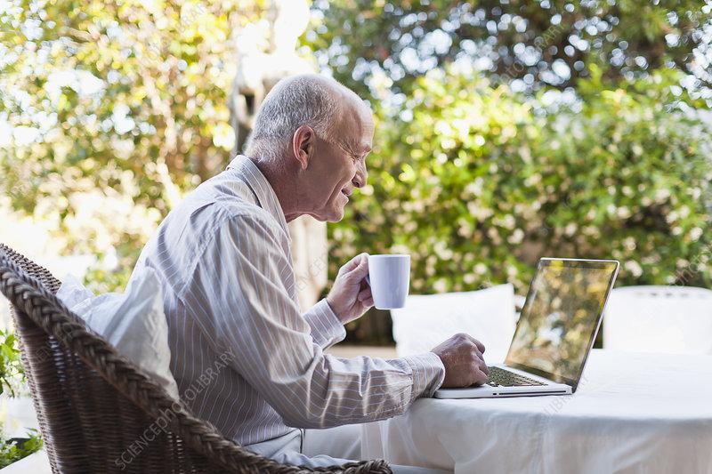 Older man using laptop outdoors