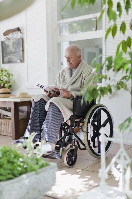 Older man reading in wheelchair