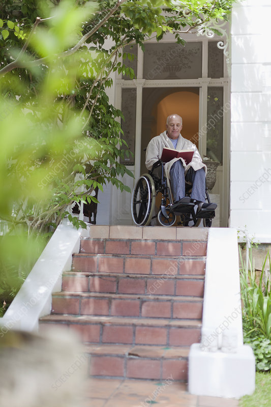 Older man reading in wheelchair