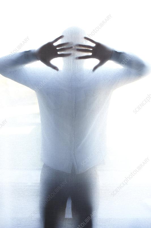 Man standing behind thin screen