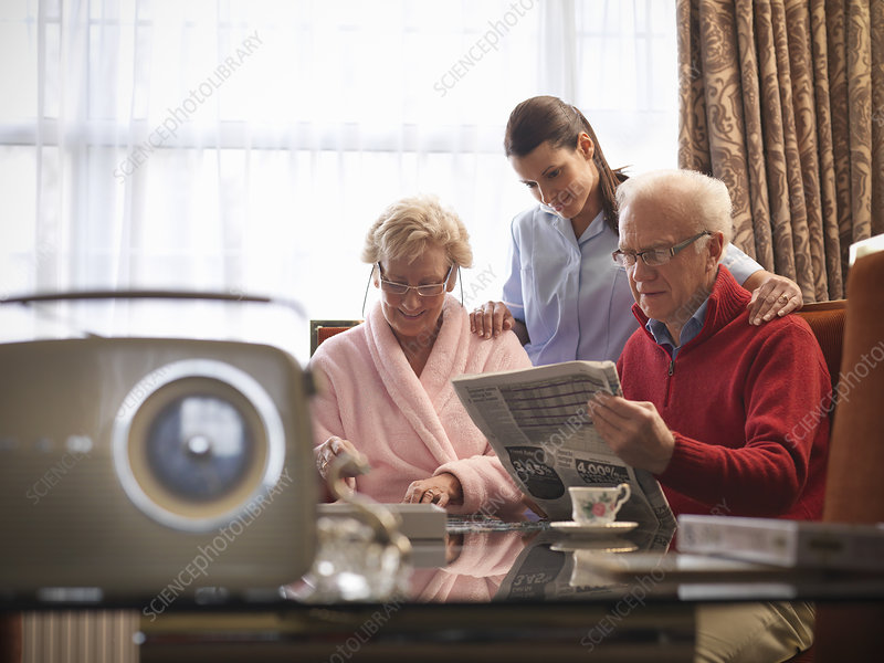 Nurse reading with older couple