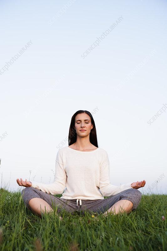 Smiling woman meditating in park